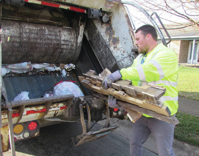 Yoder on his morning trash route in Greenville, loading unbagged wood into the back of his truck.
