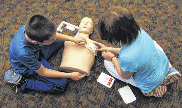 Versailles Exempted Village School District School Nurse Tracy Cordonnier has been teaching the fourth-graders compression-only CPR, due to the requirements of achieving the Heart Safe School Accreditation. Pictured are two of the students learning to use an Automated External Defibrillator (AED).