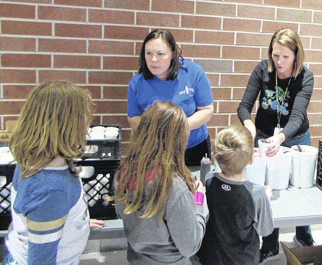 Pictured from left to right: Stephanie Baumgardner part owner of Dairy King, in Greenville, was on hand Tuesday to distribute 470 sundaes that Dairy King donated to Greenville kindergarten-second-grade students for their positive behavior. She is helped by First-grade Teacher Amy Buschur.