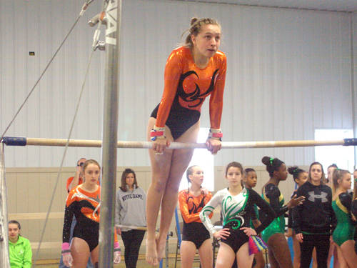 Versailles' Jorja Pothast competes on the uneven bars during the Darke-Shelby County High School Gymnastics Invitational on Saturday at Flying J's Gymnastics in Versailles.