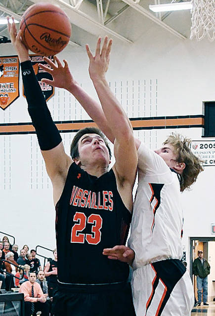 Versailles' Noah Richard shoots with pressure from Minster's Alex Lehmkuhl during a Midwest Athletic Conference boys basketball game on Friday in Minster.