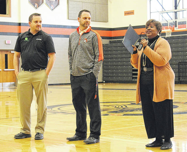State Board of Education Member Charlotte McGuire (right) congratulates Butler Middle School students and staff on achieving the state's Momentum Award for the second year in a row. Shown at left are Arcanum-Butler School Board Member Eric Moore and Superintendent John Stephens.
