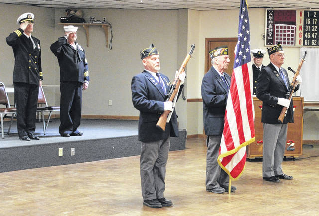 VFW post 7262 held a retirement ceremony for post commander Dean Delk Saturday afternoon. Here Delk is seen saluting, along with Navy Reserve Center commander Jim Prouty, as members of the Color Guard prepare to present an American flag to Delk's mother.