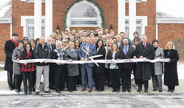 Eric and Kristin Fee (center) cut the ribbon during a Darke County Chamber of Commerce ceremony Thursday. The Fees are owners of the newly christened Tribute Funeral Homes, formerly Oliver Floyd Funeral Home in Greenville and Braund Pope Funeral Home in New Madison.