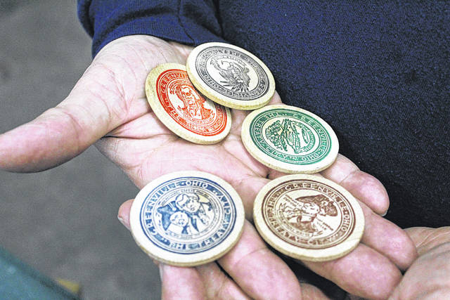 Darke County Coin Club President John Magato holds five wooden tokens from 1970, commemorating the 175th anniversary of the signing of the Treaty of Greenville. Collectors from the area gathered Sunday to the club's 52nd annual Coin Show in Greenville.