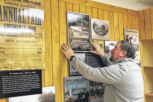 Dustin Nealeigh adjusts a facsimile of a fair poster at the Garst Museum's newest exhibit, highlighting the Great Darke County Fair. The museum is looking to opening the exhibit by the end of March.