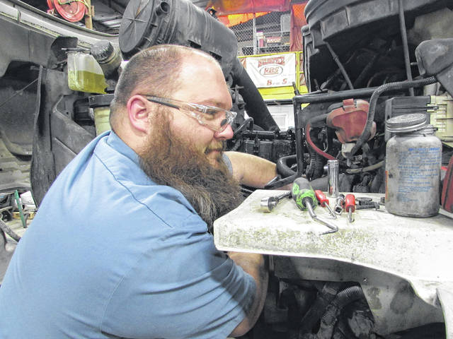 Etter hard at work on the engine of one of Rumpke's garbage trucks.
