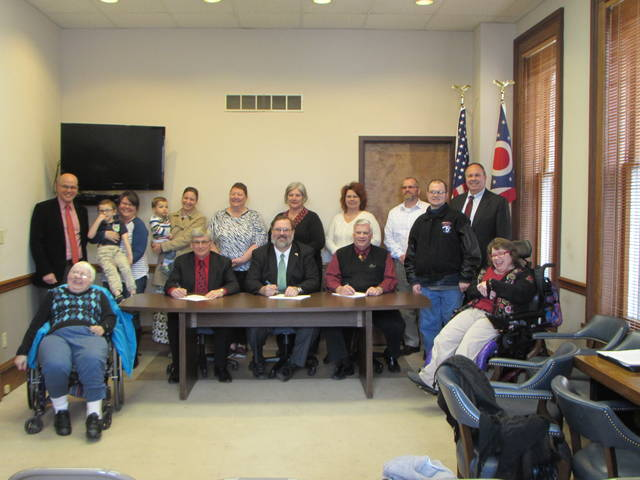 Darke County DD employers gather before the proclamation is signed. Back row, left to right, standing: Joseph Badell, Darke DD Community Services Director; Max and Tracy Conklin , Family receiving services; Laban and Alaina Kingery, Family receiving services; Gwen Tinkle, Darke DD Board Member; Pamela Neff, Darke DD Board Member; Tonya Clark, Darke DD Business Manager; Rodney Willis, Darke DD Community First Director; David Olinger, Person receiving services; Mike Beasecker, Darke DD Superintendent; Front row, seated: Ruth Wilt, Person receiving services; Mike Rhoades, Commissioner; Matt Aultman, Commissioner; Mike Stegall, Commissioner; Paula Laney, Person receiving services.