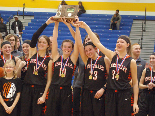 Versailles' seniors hold up their district championship trophy following a win against Purcell Marian on Monday at Springfield.