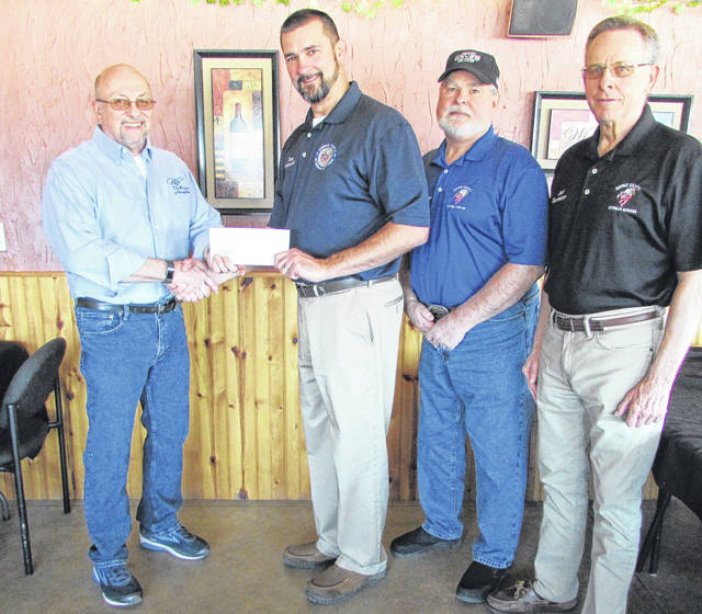 Mike Williams (far left), owner of The Winery at Versailles, presents a check to Thomas Pitman, department head of Darke County Veterans Services. Also pictured are Veterans Services Commissioners Jim Kammer and Jack Sloat.