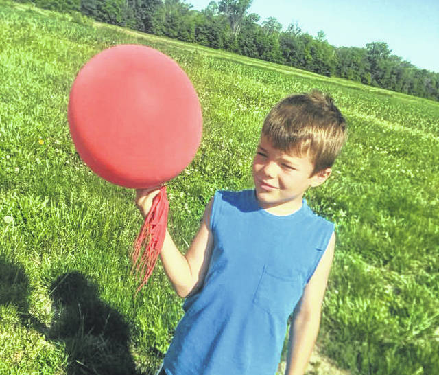 Trevar Martin, 9, son of Jeff and Mandy Martin of Greenville, holds a balloon found at the family's farm Monday morning near Greenville. Mandy hopes to make people aware of the detrimental effects of balloon launches on the environment.