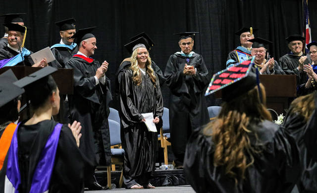 Sunny Herring, phlebotomist and Edison State alumna, receives a standing ovation following her keynote address at Edison State Community College's 43rd commencement ceremony.