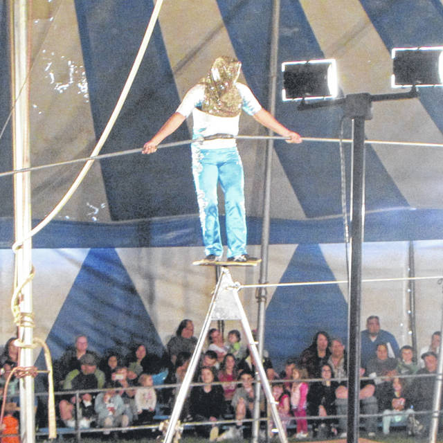 A circus performer walks the tight rope blindfolded, nearly missing the end of the platform at the circus Monday evening.