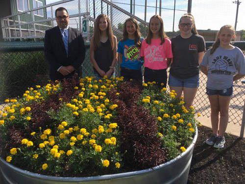 "Greg Zechar looks over the project of ""Hero"" marigolds and ""Red thread"" alternanthera with Butterflies Junior Garden Club members Kate Rehmert, Saige Fellers, Brianna Fellers, Grace Spect and Kendall Cromwell."