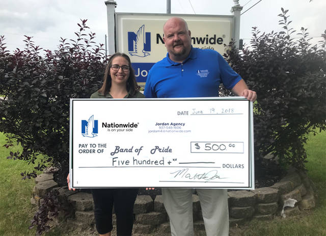 Matt Jordan, owner Jordan Agency, presents a check to Sara Lewis, GHS band director, as the Gold Sponsor of the inaugural Band of Pride 5K on Saturday at the Cardinal Center in Gettysburg.