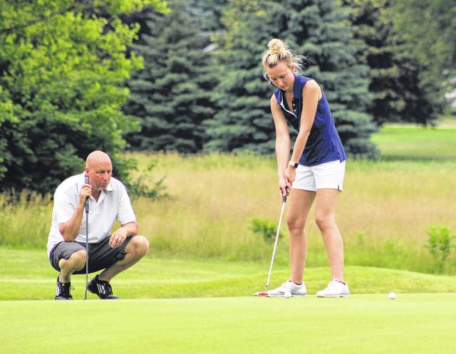 Lindy Cummings putts on the No. 13 green while playing in the ninth annual Karlh McCallister Memorial Golf Tournament on Saturday at Turtle Creek Golf Course. Her father, Lonnie Cummings, kneels behind lining up his putt.
