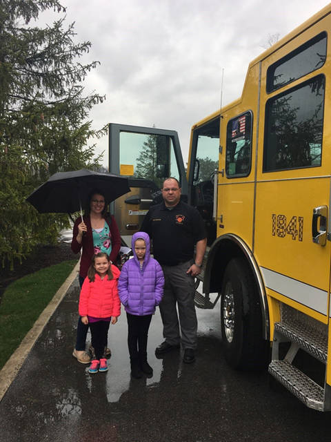 Kristy Wehrkamp and daughters Kendall and Makayla are pictured with Fire Chief Brian Pearson of the Versailles Fire Department.