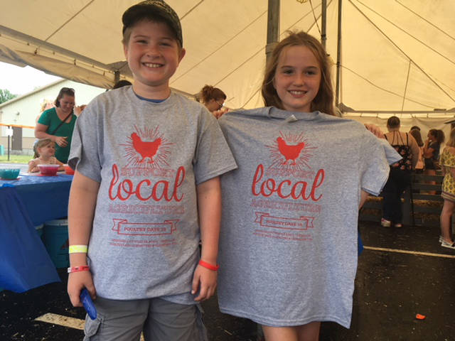 Two youth proudly display the T-shirts sponsored by Weaver Egg's and Versailles Poultry Day committee that they won as part of answering an agriculture question as part of spinning the wheel.