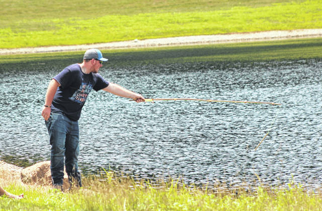 Trenton Turvene throws his fishing pole into the pond during the last day fishing tournament at Chenoweth Trails.