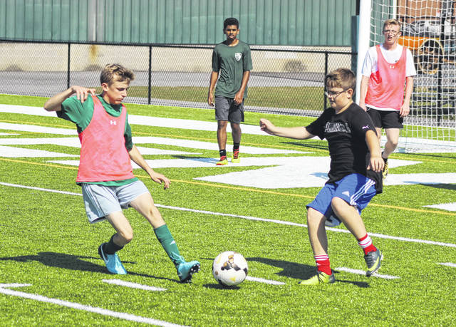 These players battle for the ball on Thursday morning during the fourth day of the Greenville boys soccer team camp at Greenville's Harmon Field.