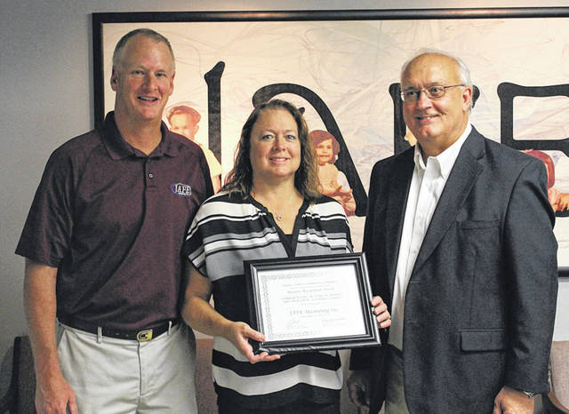JAFE Decorating Owners Randy and Lisa O'Dell receive a Business Recognition Award from Tony Roberts of the Darke County Chamber of Commerce. The company celebrated its 40th anniversary Friday.