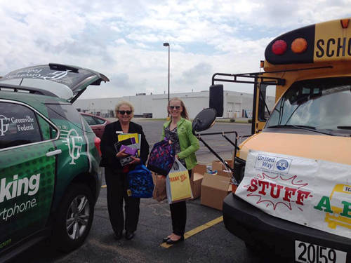 """Betty Hartzell and Susan Barker from Greenville Federal drop off school supplies during the 2017 """"Stuff A Bus"""" event."""