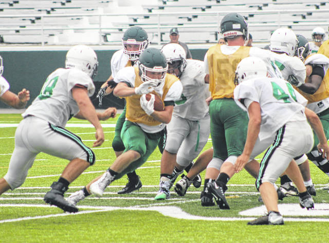 Greenville's Landon Eldridge looks for a hole to run through against Celina during the Green Wave's first scrimmage game on Tuesday at Harmon Field.