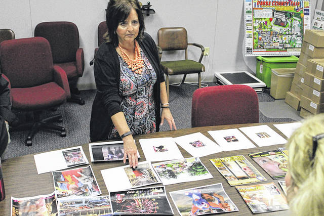 Greenville National Bank's Lisa Martin looks through submitted photos for <em>The Daily Advocate's</em> Fair Magazine cover.