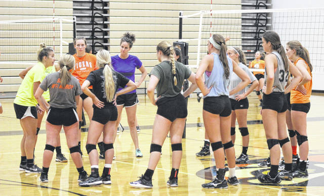 Versailles volleyball coach Kenzie Bruggeman (far left) talks to her players after an intense practice on Tuesday. The Tigers are the defending Division III state volleyball champions and are gunning for a repeat title run, but will have to do it with many new faces on the court this season.