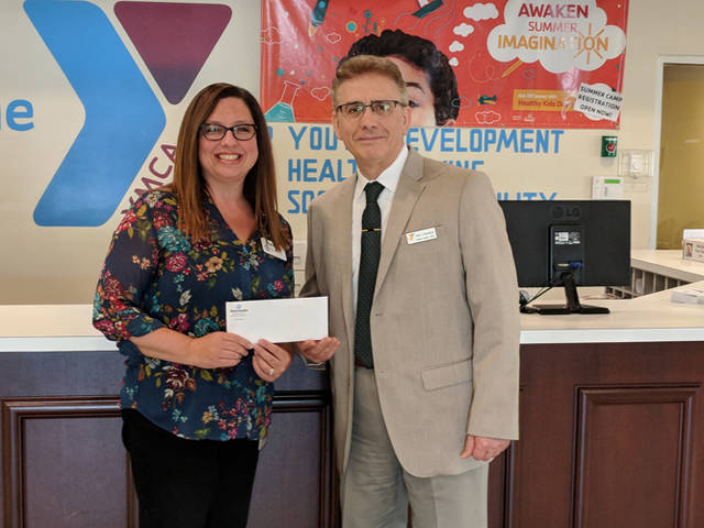 Angela Cline (left), director of Reid Health Community Benefit, presents a grant check for $5,700 to Sam Casalano, CEO of the YMCA of Darke County, to support the launch of a new weight loss program at the YMCA.