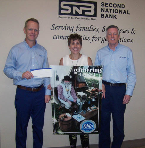 Second National Bank Vice President Todd Durham and President John Swallow present a check to Gathering at Garst committee member Katie Gabbard.