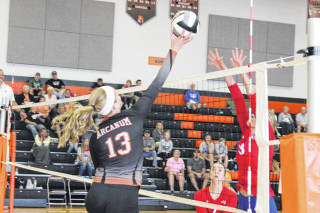 Arcanum's Taylor Gray (13) with a smash over the net during the Trojans' second round match against Tri-Village on Saturday in the Darke County Volleyball Invitational held at Arcanum. The Trojans won the overall championship later in the day by defeating Franklin-Monroe in the finals.