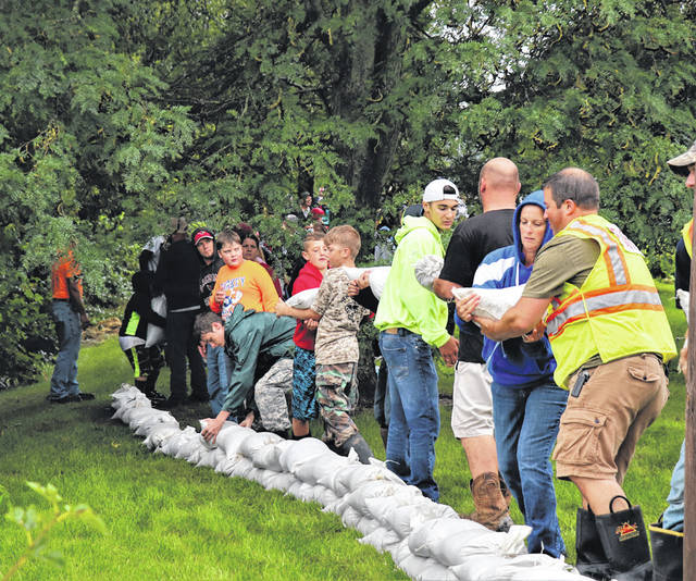 Volunteers pile sandbags near the creek in New Madison. The village received nearly 5 inches of rain Saturday, with more rainfall expected Sunday and Monday.