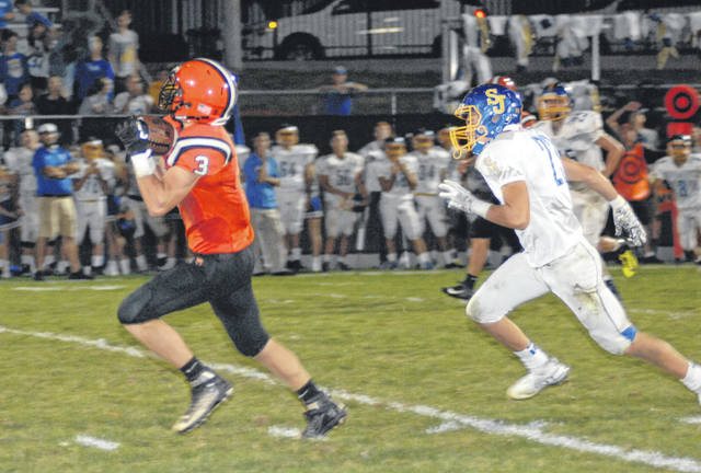 Versailles' Andrew DeMange runs away from a Delphos St. John's defender during the Tigers 27-0 win on Friday night. DeMange had 97 receiving yards and a touchdown in the game.