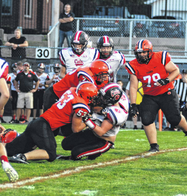 Ben Albers (53) and a Versailles teammate tackle a Delphos Jefferson runner on Friday night. The Tigers won their first game of the season, 47-14.