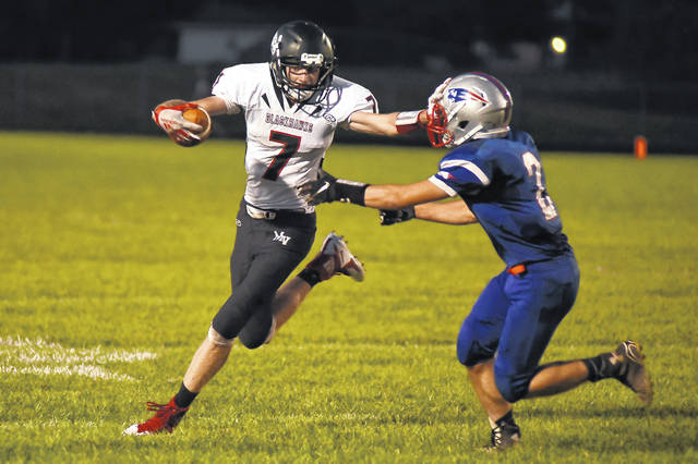 Mississinawa Valley's Blake Scholl (7) gives a stiff arm to Tri-Village defender Drew Medaris (2) during a run on Friday night. The Blackhawks won the scoring fest 44-28.