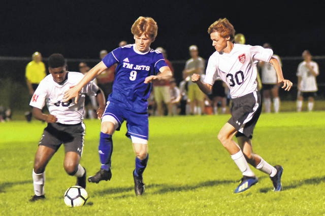 Franklin-Monroe's Brydon Diceanu (9) battles for the ball with two Newton defenders in a Cross County Conference contest Tuesday night. The Jets lost the game, 2-0.