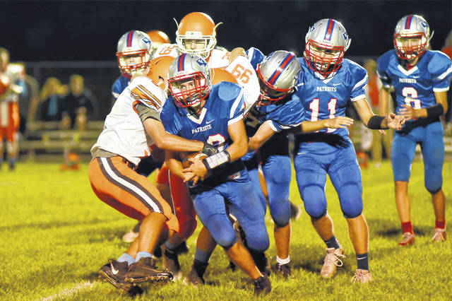 Tri-Village's Derek Eyer (20) tries to get away from several National Trail defenders during the Patriots home game on Friday night. The Blazers won the game, 45-8.