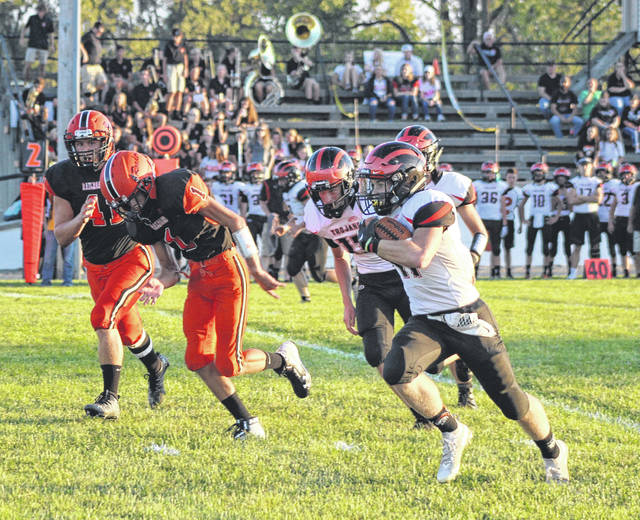 Arcanum's Devin Keckler (11) gets around the end on a 31-yard touchdown run in the first quarter Friday night at Bradford. The Trojans won the game 48-7.