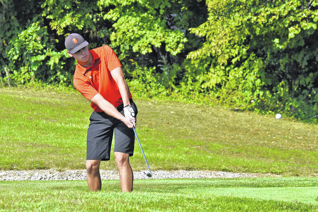 Arcanum's only senior Evan Atchley chips onto a green during the Cross County Conference boys golf tournament on Thursday at Stillwater Valley Golf Course. The Trojans finished fourth in the team standings.