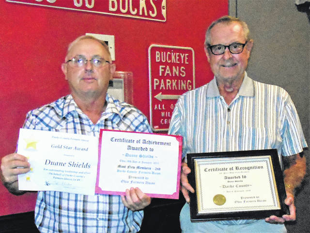 Former Darke County Farmers Union President Duane Shields is shown with awards presented by current President Todd Rhoades.