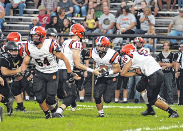 Versailles running back Jake Poling (6) takes the ball from quarterback Ryan Martin on this play at Rockford Parkway on Friday night. The Tigers fell to the host Panthers 21-7.