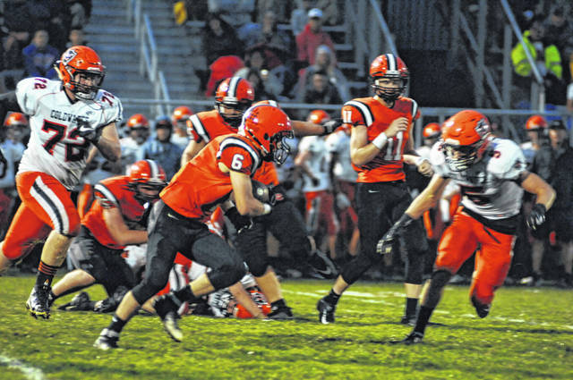 Versailles' Jake Poling (6) runs away from a pair of Coldwater defenders during their Midwest Athletic Conference game Friday night. Poling scored the Tigers only touchdown in a 35-7 loss to the Cavaliers.