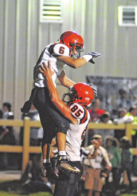 Jake Poling (6) is lifted high in the air by Evan Hiestand (85) as the two celebrate a Versailles touchdown Friday night against Midwest Athletic Conference host Anna. The Rockets won the game, 41-21.
