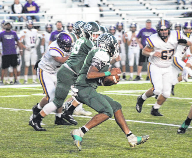 Greenville's Marcus Wood (1) looks for an open lane to run through after he intercepted a pass from Butler quarterback Mason Motter during the first half of Friday night's game at Harmon Field. Butler won the game, 37-21.