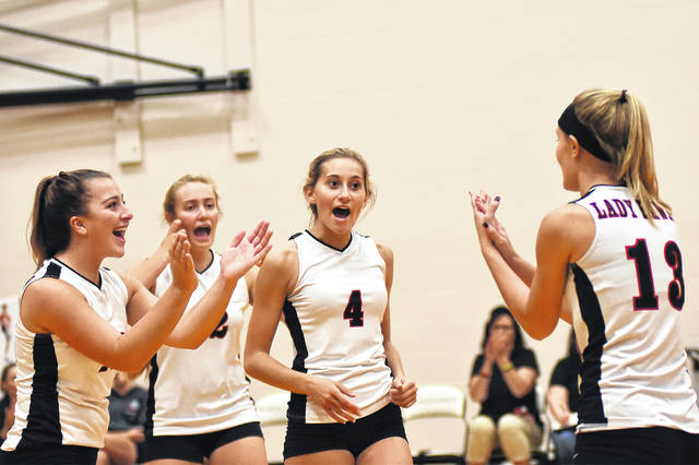 Olivia Murphy (4) and her teammates celebrate after a point during Mississinawa Valley's home match with Union City (Ind.) on Monday night. The Blackhawks swept the Indians in three sets to win the border battle.