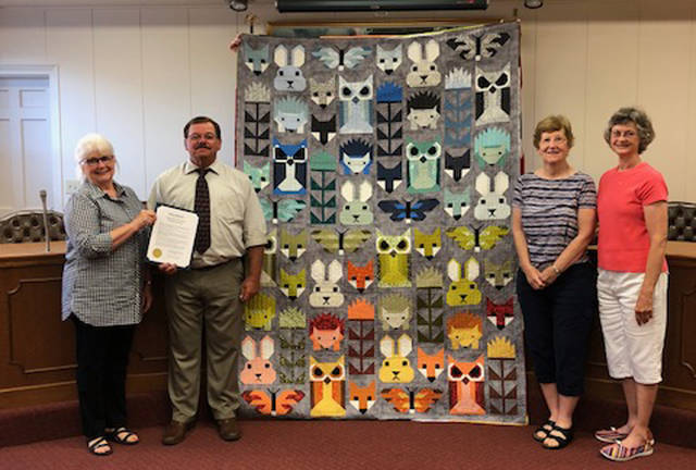 Greenville Mayor Steve Willman signed a proclamation declaring the week of Sept. 23 to 29 as Quilt Week. Pictured with him and the Fancy Forest quilt by Elizabeth Hartman are Towne Squares Quilt Club members Toni Heggie, Amy Litke and Nancy Brumfield. Not pictured is Joyce Mikesell.