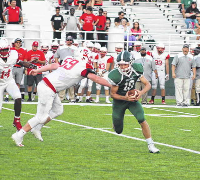 Greenville quarterback Tyler Beyke (18) avoids a sack late in the first quarter then picks up some blockers and rumbles 20 yards for a touchdown to put the Green Wave ahead 21-0 against Stebbins in the home-opener Friday night at Harmon Field. Greenville went on to win the game 49-19 to improve to 2-0 on the season.