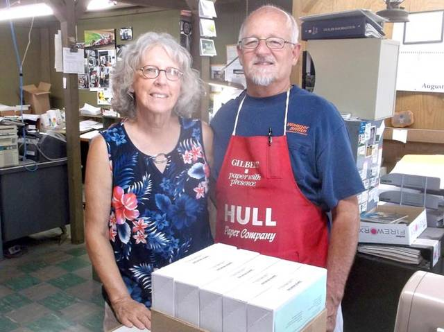 Empowering Darke County Youth Assistant Program Coordinator Kay Sloat poses with Bob Claudy, owner of Rapid Printing, while picking up this year's Empowering After School Program signup sheets.