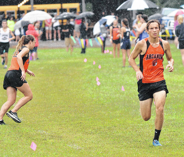 Arcanum's Tanner Delk nears the finish line during the rain-soaked Covington Invitational on Saturday. Delk was the overall race champion with a time of 16 minutes, 57.3 seconds.